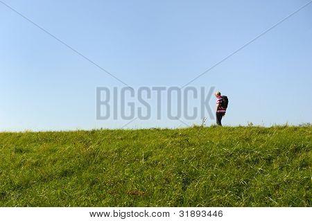 Elderly man is walking alone at the Dutch dike