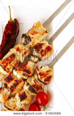fresh grilled  pork shish kebab on white platter