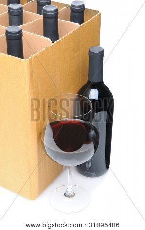 A wineglass and bottle in front of a case of wine bottles. Vertical format over a white background.