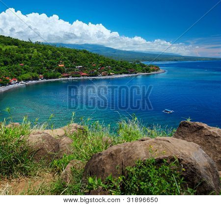 Tropical lagoon with clear water, bush green meadow and buildings in forest on a hillside. Amed village, Indonesia