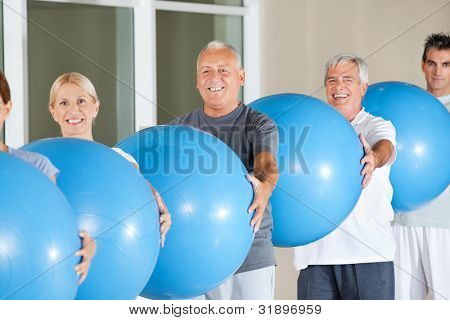 Happy senior group doing fitness exercises with blue gym balls