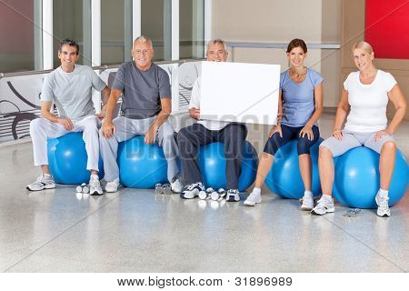 Senior fitness group in gym with empty sign