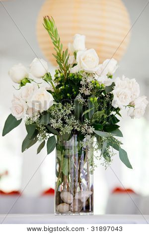 a large white wedding centerpiece on a table, white roses