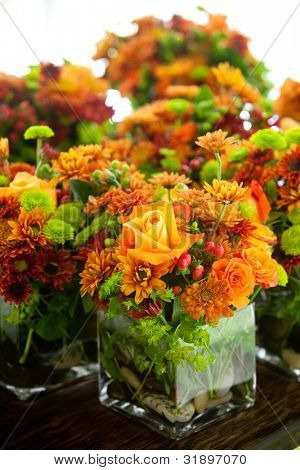 a group of wedding centerpieces in glass jars. orange and green colors