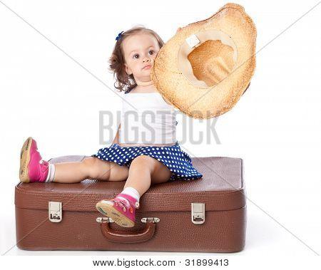 eine Mädchen sitzt auf einem Koffer. isoliert auf einem weißen Hintergrund.