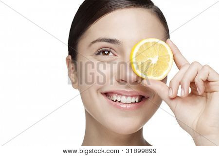 young woman holding lemon slice in front of eye. All skin detail has been kept, no filters used