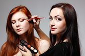 Portrait of beautiful young redheaded woman with esthetician making makeup eye shadow poster
