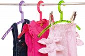 Girls Clothes On Rack. Close-up Of Colorful Stylish Summer Dresses And A Short Pants For The Little  poster