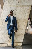 Young African American Businessman Talking On Cell Phone Outside In New York, Wearing Blue Suit, Whi poster