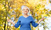 zen, relax and old people concept - portrait of smiling senior woman in blue sweater chilling over a poster
