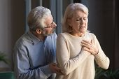 Worried Elder Husband Helping Wife Touching Chest Having Heart Attack poster