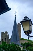 Street Light, Pfarrkirche Church And Lowenburg Castle In The Background At The Picturesque Village O poster