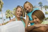 stock photo of early 60s  - Girls and Grandmother Watching TV at Pool - JPG