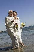 stock photo of early 60s  - Senior Newlyweds Walking in Ocean - JPG