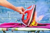 An Overheated Clothes Iron Ignited On An Ironing Board, A Fire Started In The House, A Hand Raises A poster