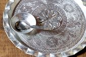 Silver Plate And Silver Bowl With Silver Spoon On Wooden Table poster