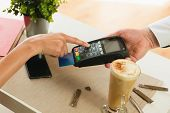 Customer Making Payment Using Credit Card.waiter Holding Credit Card Swipe Machine While Customer Ty poster