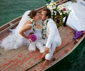 foto of wedding couple  - young couple in wedding dress kissing in the boat - JPG