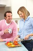 Mature couple preparing meal in domestic kitchen poster