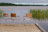 Idyllic View Of The Wooden Pier In The Lake With Chairs For Negotiations poster