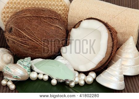 Coconut spa products with moisturiser, exfoliating scrubs, sea shells and pearls over bamboo background.