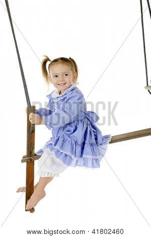 An adorable preschooler swinging herself in her frilly dress and bloomers on a rustic, antique, 2-person swing.  On a white background.