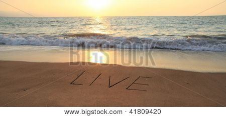 The word Live hand written in the sand at sunset.