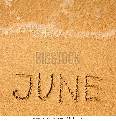 June - written in sand on beach texture - soft wave of the sea.