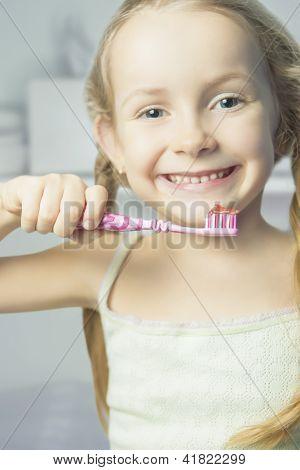 Portrait Of Little Smiling Girl Brushing Her Teeth