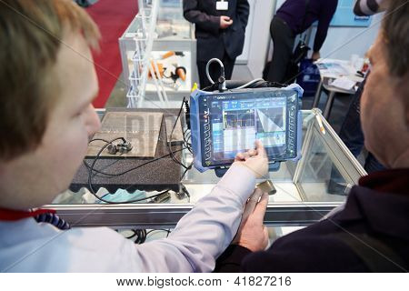 MOSCOW - FEB 28: Company representative explains operation of portable modular defectoscope to visitor of exhibition ExpoCoating 2012 in Olimpyisky Sport Complex, Feb 28, Moscow, Russia.