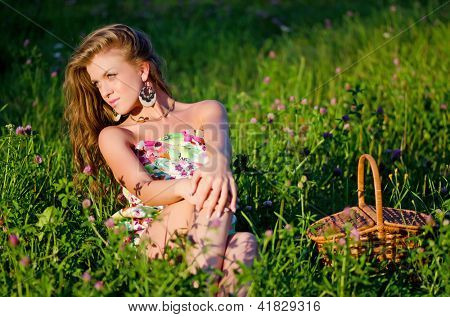 Girl sits in grass with a basket on a sunset
