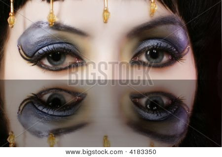 Ancient Egyptian woman - Cleopatra with gold dress eyes close-up