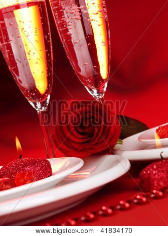 Image of beautiful Valentine day dinner still life, two glasses for champagne, alcohol beverage, romantic drink, sparkling wine, red rose and candle, festive table setting, love concept