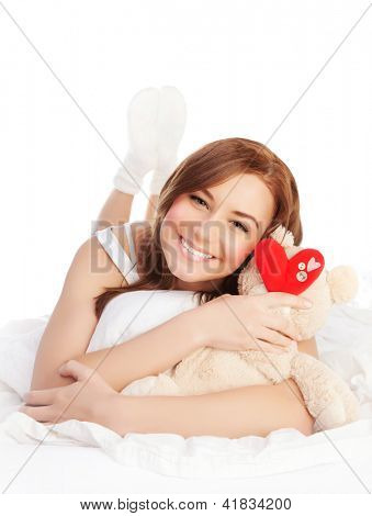 Picture of happy woman laying down in bed linen and enjoying romantic present, soft bear and red handmade heart-shape toy as gift for Valentines day holiday, isolated on white background, love concept