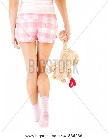 Conceptual image of one-sided love, rear view of woman wearing pink shorts and socks and holding teddy bear in hand, break up, broken heart, first unhappy love, sadness and loneliness concept