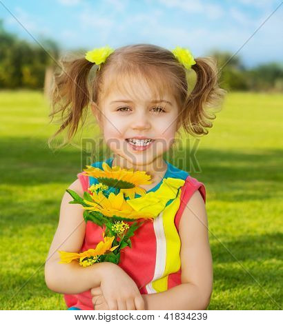 Picture of cute happy little girl wearing colorful dress and holding in hands beautiful sunflower bouquet, adorable small female in garden with fresh yellow flowers, sweet child having fun outdoor