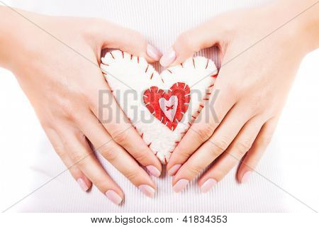 Picture of a small white heart in hands, female holds handmade sewn soft toy, macro, shallow dof, woman with Valentine gift, happy girl smiling, conceptual image of health care or love