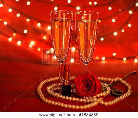 Photo of two wine glasses, red lipstick, luxury white pearl beads, fresh rose flower, romantic dinner in restaurant, festive decorations, beautiful accessories, Valentine day, love concept