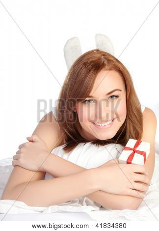 Picture of a happy young woman with gift box, cheerful female relaxing, laying down in the bed, isolated on white background, pretty girl portrait with romantic present, holiday celebrations concept