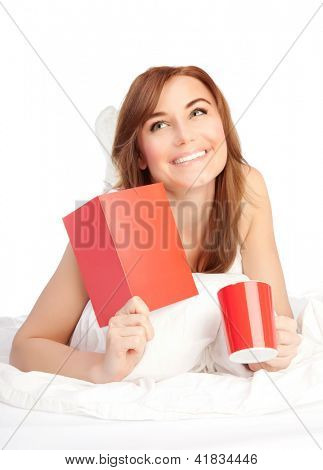 Happy woman laying down in the bed, girl got romantic Valentine greeting card present, drinking coffee on holiday morning, female relaxing at home, isolated on white background, love concept