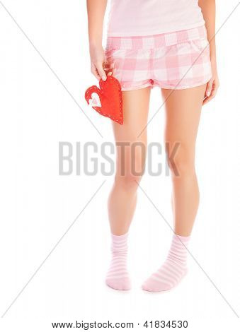 Picture of young woman holds red heart soft toy, body isolated on white background, female legs, lonely heartbroken girl wearing pajamas, one-sided love and parting in relationship concept