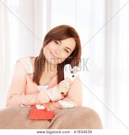 Image of beautiful woman sitting on the bed at home and covered with blanket holding handmade sew heart, Valentine day, romantic gift, lovely female, 14 of february, love and happiness concept