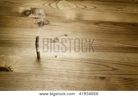 Smoking cigarette on wooden background