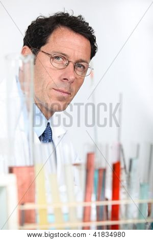 Chemist with rack of test tubes
