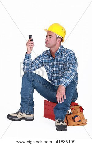 Man sat on tool box sending text message