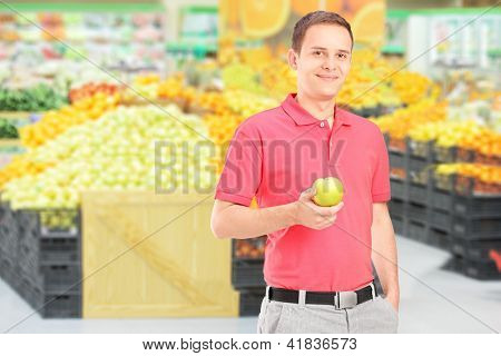 Young man standing in a supermarket and holding an apple