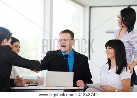 Happy business people shaking hands on a deal and smiling over working table