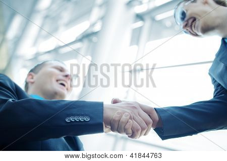 Business shaking hands in front of modern steel and glass building