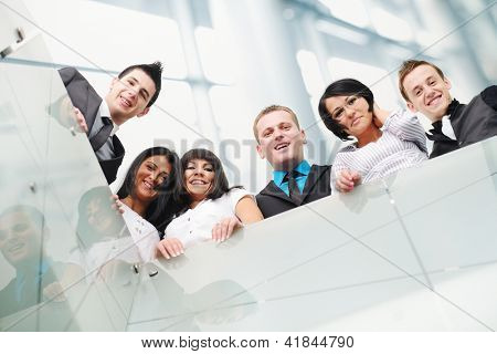 Group of business people standing inside the modern glass building