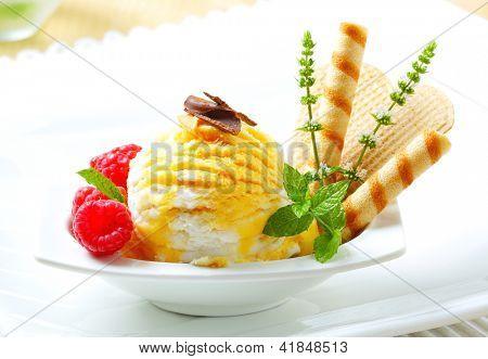 Eisbecher mit gelber fleckiger Eis, Himbeeren und Kekse